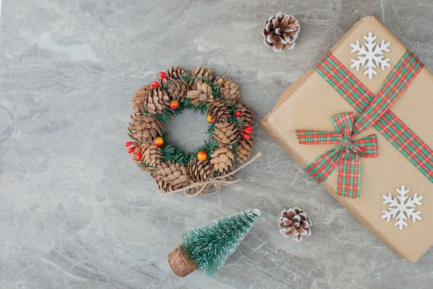 Christmas gift box, pine tree and wreath on marble.