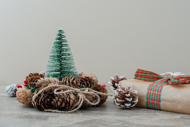 Christmas gift box, pinecones and wreath on marble table.