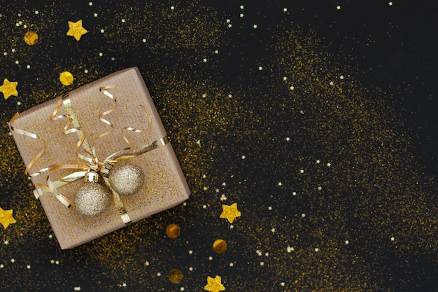 Christmas gift box or present decorated golden ribbon and two balls on black background with sparkles.