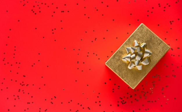 Christmas gift box on red background. flat lay, top view, copy space.
