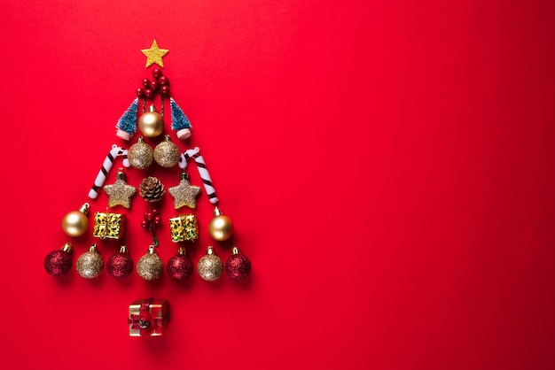 Christmas gift box, red ball and bell in shape of christmas tree, red background.