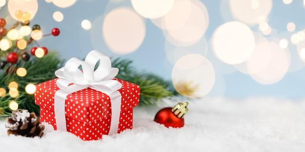 Рождественская подарочная коробка, красный шар с золотыми огнями на синем фоне