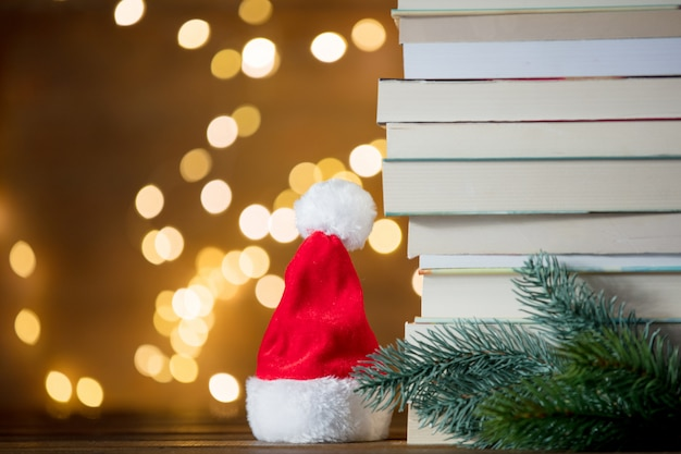 Christmas gift box, santa claus hat and pile of books