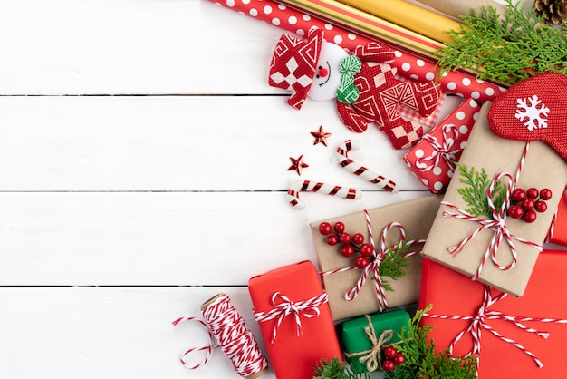Christmas gift box, spruce branches and decoration wooden background.