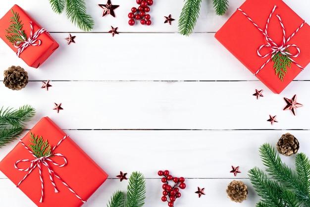 クリスマスのギフトボックス、スプルースの枝、松のコーン、木の背景に赤い果実。