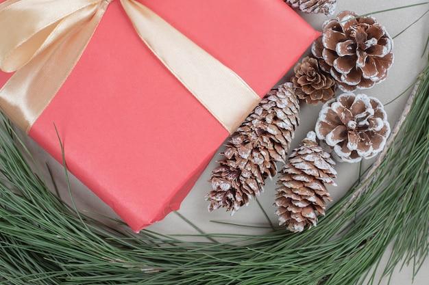 Новогодняя подарочная коробка, перевязанная лентой и шишками