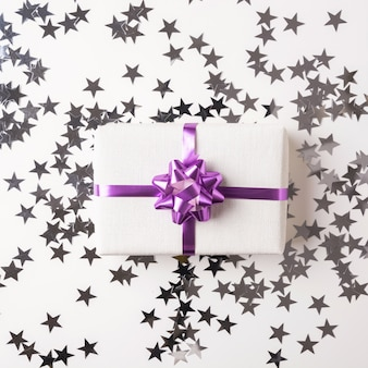 Christmas gift box on white table with silver star