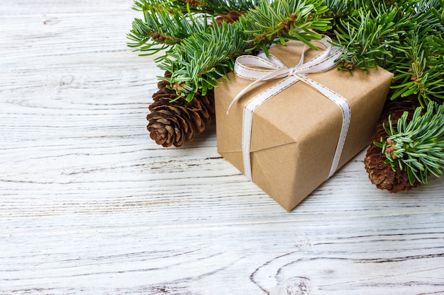 Christmas gift box on the white wooden table ,spruce branch,pine cones,frame,top view,