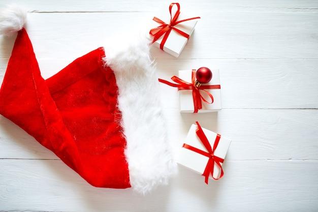 クリスマスギフトボックスウィットサンタ帽子、白い木製の背景に赤い装飾、クリスマス、冬、新年のコンセプト、フラットレイ、上面図、コピースペース