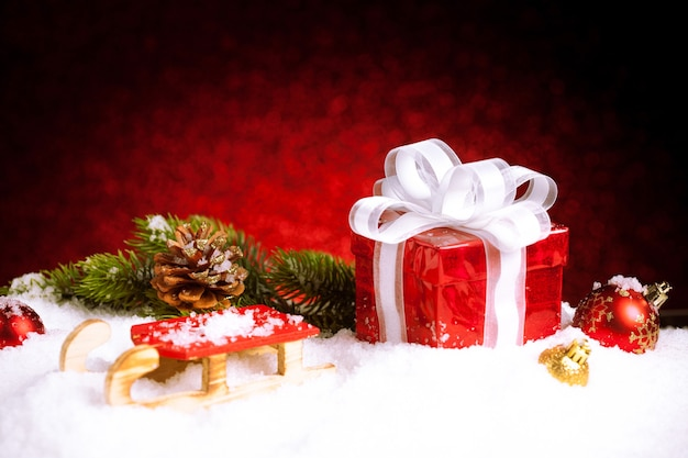Новогодняя подарочная коробка с шарами, звездами и украшениями на снегу