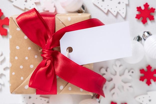 Рождественская подарочная коробка с пустой подарочной биркой, вид сверху, макет