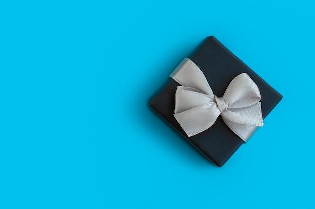 Рождественская подарочная коробка с бантом на синем фоне, для макета или дизайна, место для copyspace