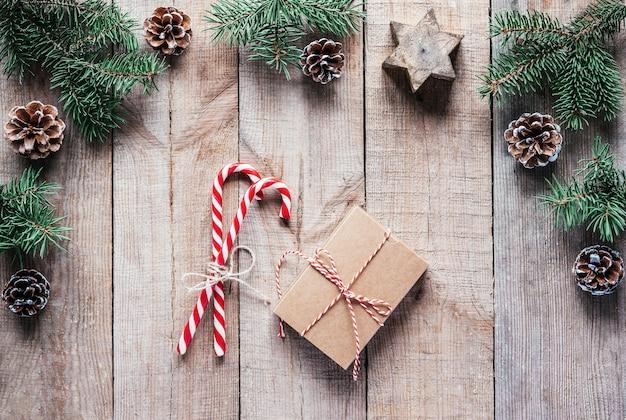 나무 배경에 사탕 지팡이와 전나무 나뭇가지가 있는 크리스마스 선물 상자