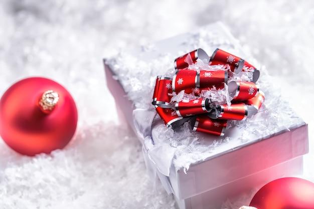 抽象的な雪のシーンでクリスマスボールとクリスマスギフトボックス