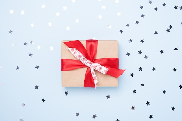 Christmas gift box with confetti stars on blue background
