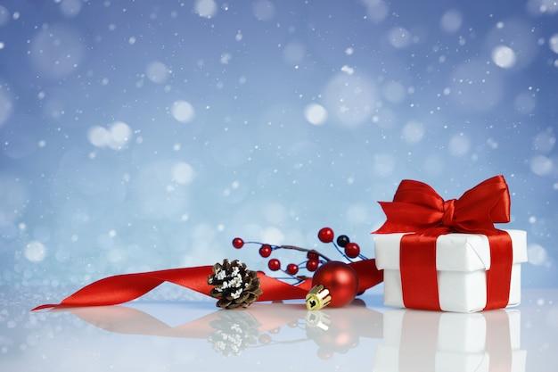 Рождественская подарочная коробка с украшениями на синем фоне