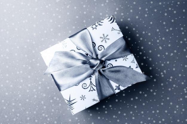 Рождественская подарочная коробка с луком diy на серой поверхности с нарисованным снегом.