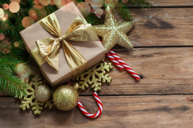 Christmas gift box with fir branches and holiday decoration on wooden background