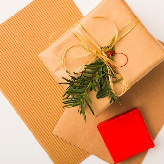 Christmas gift box with golden ribbon and fir branch