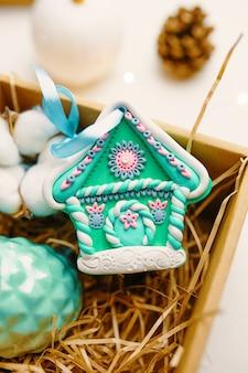 華やかなジンジャーブレッドハウスと綿のクリスマスギフトボックスは、polで作られたお祝いのお土産のクローズアップ...