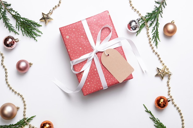 Christmas gift box with paper tag and christmas decorations on white background. winter, new year concept. flat lay, top view, copy space.
