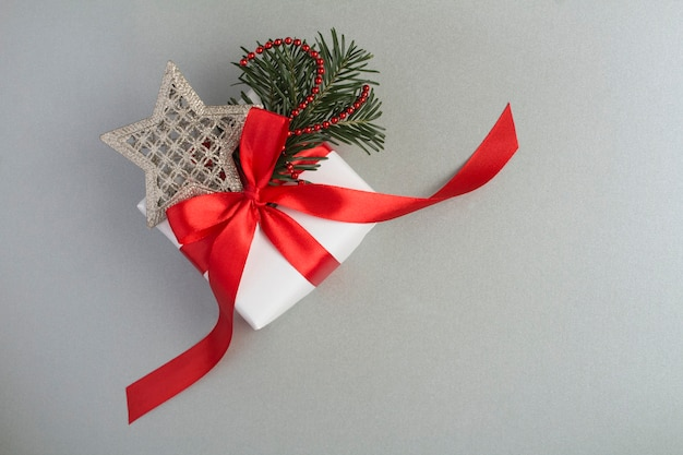 Christmas gift box  with red ribbon on the gray background. top view. copy space.