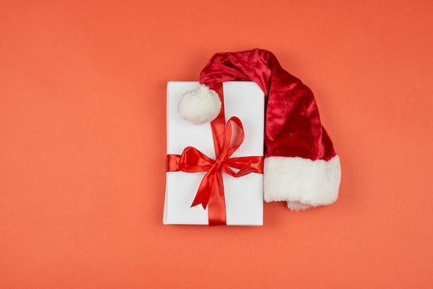 赤い背景にサンタクロースのキャップが付いたクリスマスギフトボックス