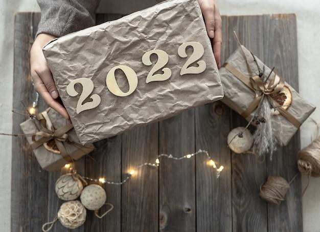 Confezione regalo di natale con numeri in legno 2022 in mani femminili sullo sfondo di decorazioni festive.
