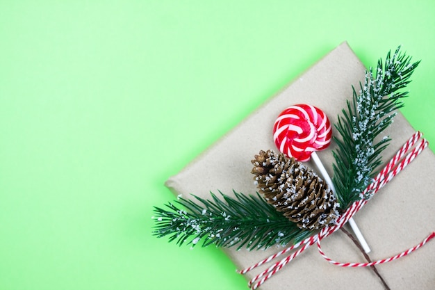 Christmas gift box wrapped in brown craft paper with corn, fir-tree and candy on green background. christmas concept. eco package. focus on corn