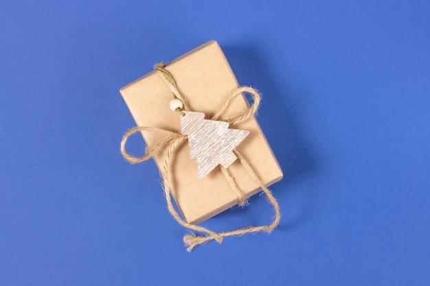 青い背景にクラフト紙で包まれたクリスマスギフトボックス。上面図、休日、クリスマスのコンセプト。