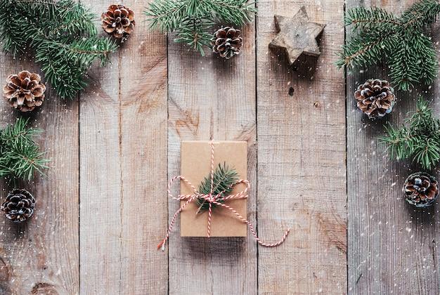 나무 배경에 크리스마스 나무 가지가 있는 크라프트지에 싸인 크리스마스 선물 상자