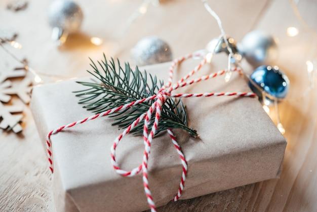 크리스마스 조명과 장식이 있는 소나무 가지가 있는 크라프트지에 싸인 크리스마스 선물 상자