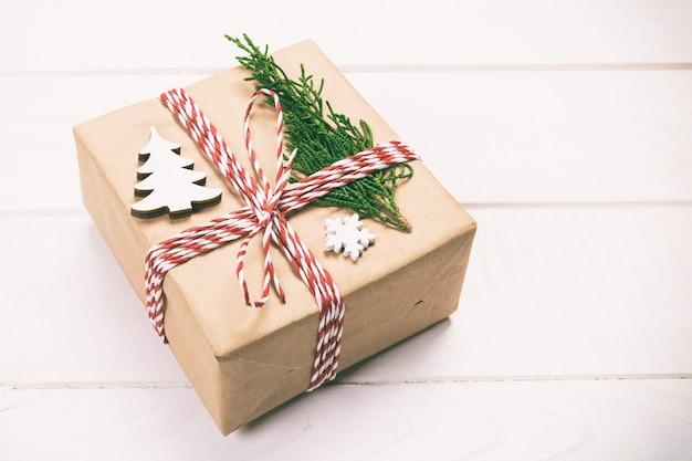 재활용 종이로 포장된 크리스마스 선물 상자, 소박한 배경에 복사 공간이 있는 리본 위쪽 전망. 휴일 개념입니다. 톤.