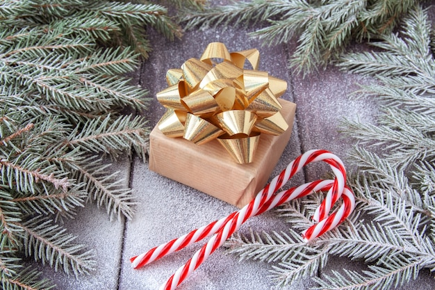 Christmas gift box wrapped in kraft paper with gold ribbon and red christmas sweets on snow covered dark wooden background