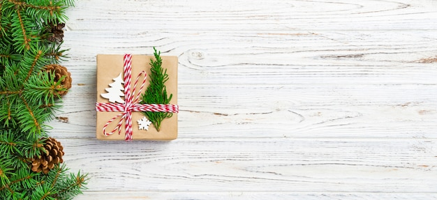 Christmas gift box wrapped in recycled paper, with ribbon bow, with ribbon on rustic background
