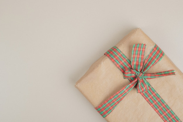 Christmas gift box wrapped in recycled paper with ribbon bow