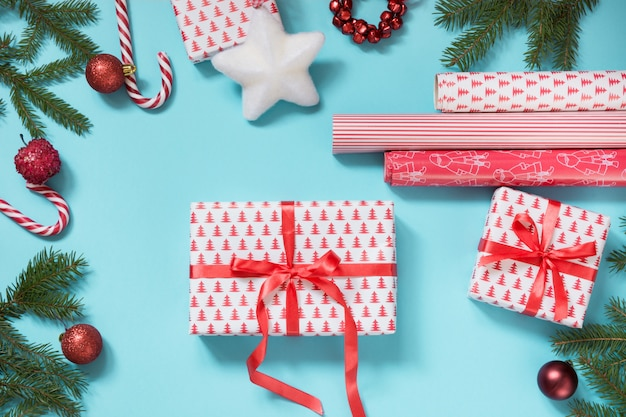 Christmas gift box wrapped with red ribbon and workspace on blue.