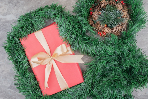 Christmas gift box and wreath on marble.