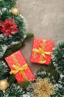 灰色の木製の背景にクリスマスギフトボックスと装飾。上面図。垂直