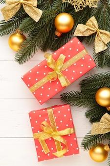 白い木製の背景にクリスマスギフトボックスと装飾。上面図。