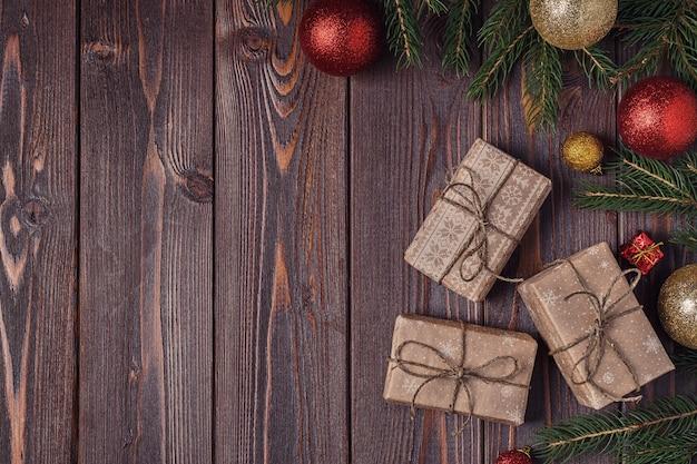クリスマスのギフトボックスと木製の背景にモミの木