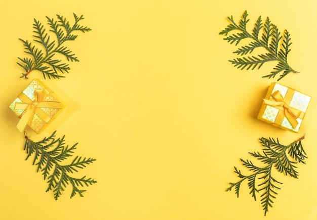 Рождественские подарочные коробки и зеленые ветви на желтом фоне. вид сверху.