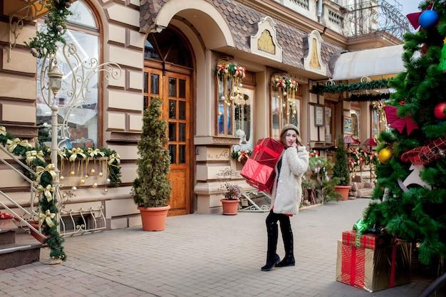 크리스마스 선물 상자와 크리스마스 트리 아래 쇼핑 패키지는 흰색 카펫에 놓여 있습니다