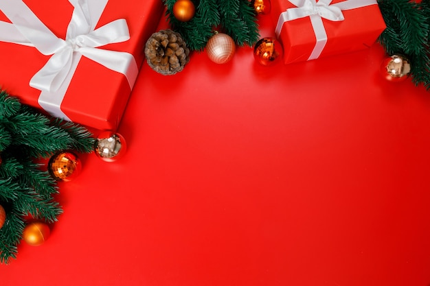 Christmas gift boxes, baubles and fir branches on red background, closeup