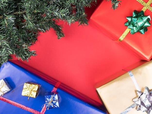 Scatole regalo di natale e albero di natale su sfondo rosso. ornamento di tradizione.