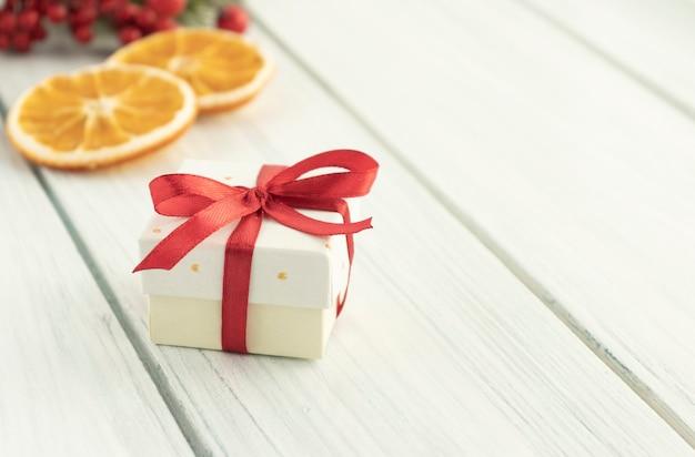 Рождественские подарочные коробки, украшенные зелеными ветками и елочными шарами. новогодняя композиция.