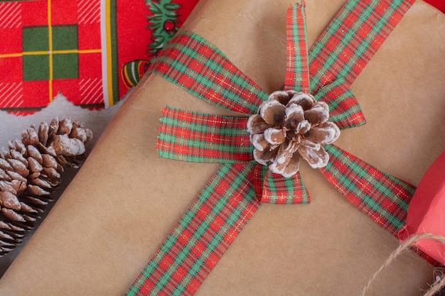흰색 표면에 소나무 콘으로 장식 된 크리스마스 선물 상자