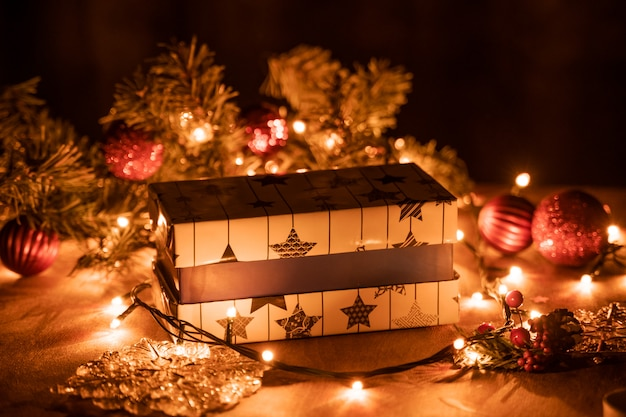 Christmas gift boxes decoration with christmas tree and candle lights on the wooden table with bokeh lights