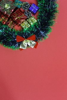 Christmas gift boxes and decorations on red art paper background.