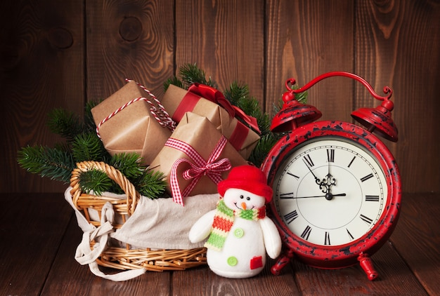 Christmas gift boxes and fir tree branch in basket with alarm clock and snowman toy